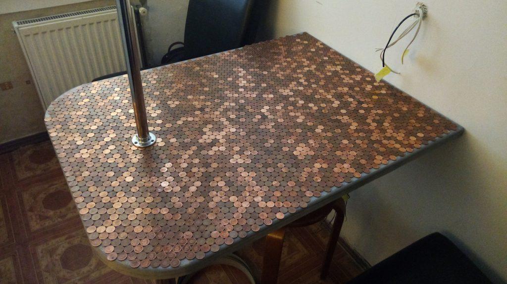 Стол из монет выглядит незаконченным по периметру, нужно резать монеты и вставлять кусочки